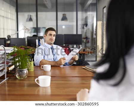 caucasian HR manager looking at a female candidate during an interview. - stock photo