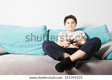 Caucasian kid playing video game while sitting on couch legs crossed - stock photo