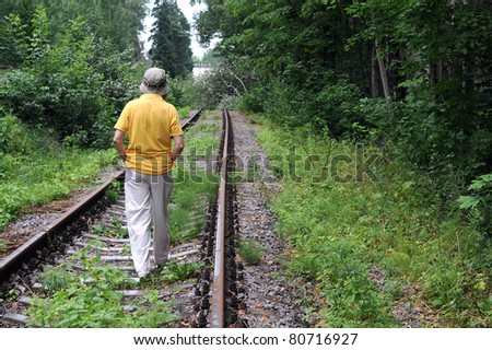 Caucasian lady walking down abandoned railroad track