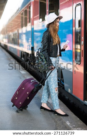 caucasian lady with a luggage traveling by train - stock photo