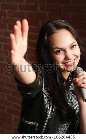 Caucasian lady with a microphone singing against a brick wall - stock photo