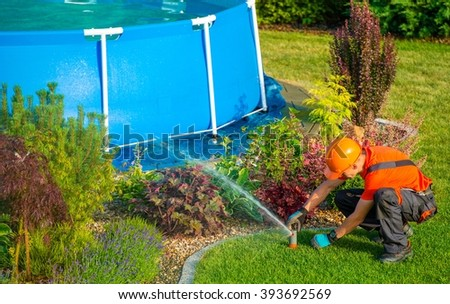 Caucasian Lawn Garden Technician in the Residential Garden with Swimming Pool Taking Care of Lawn Sprinklers System. - stock photo