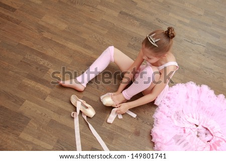 Caucasian little ballerina puts on pointes while sitting on an old wooden floor in the ballet hall - stock photo