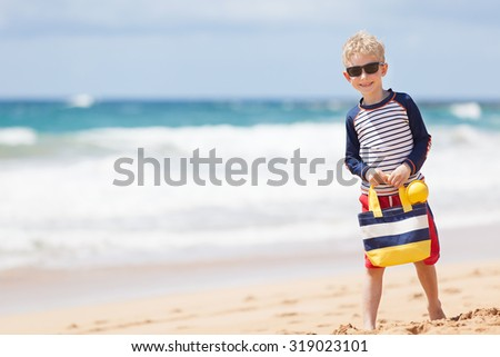 caucasian little boy in swimwear and rashguard holding beach bag enjoying time at the beach - stock photo