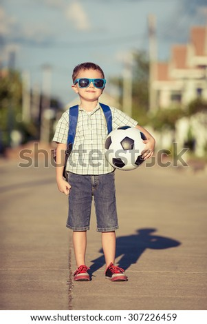 Caucasian little boy standing on the road and holding his soccer ball under his  hands at the day time - stock photo