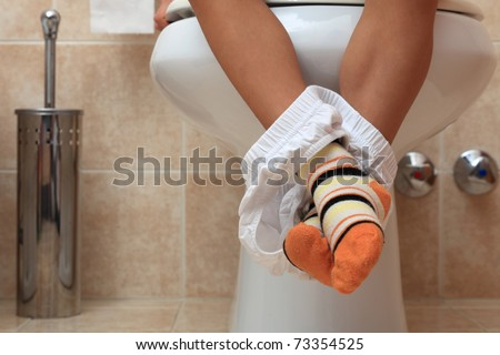 caucasian little child in toilet, low view on legs and foots - stock photo