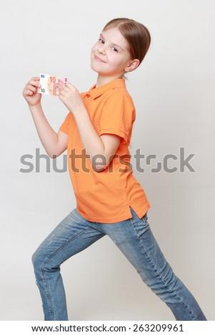 Caucasian little girl holding euro - stock photo