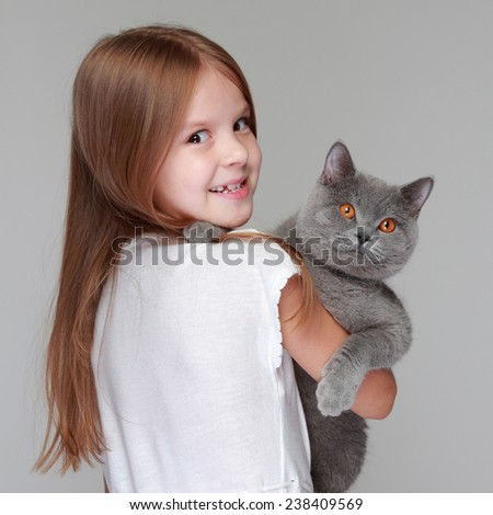 Caucasian little girl holds her cat in the arms - stock photo