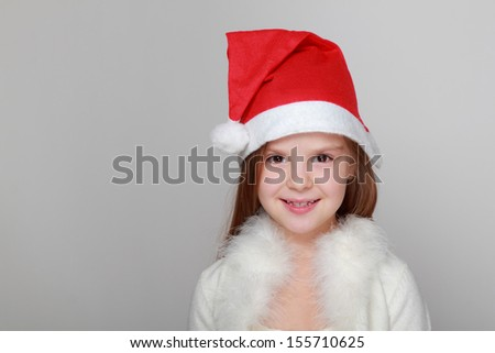 Caucasian little girl in red santa hat on gray background on Holiday