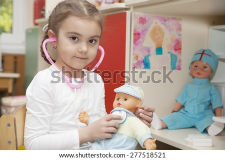 Caucasian little girl playing doctor with a doll in the nursery  - stock photo