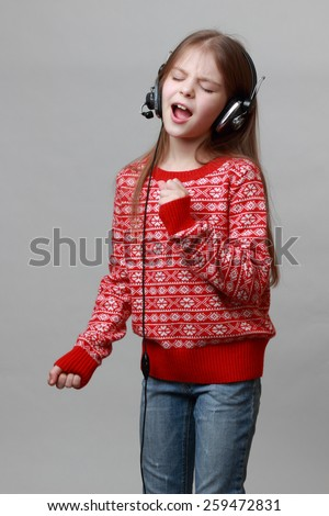 Caucasian little girl wearing red christmas sweater is singing - stock photo