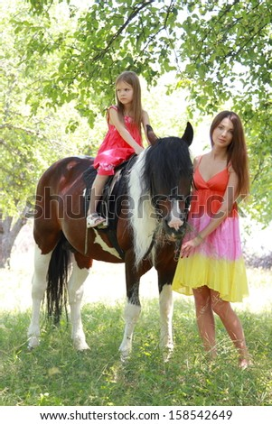 Caucasian little girl with her mother learns to ride a horse in a summer apple garden