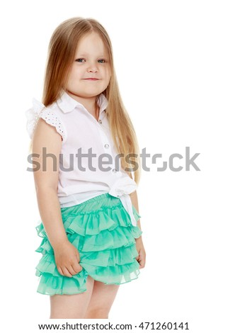 Caucasian little girl with long blond hair below the shoulders ,in a short green skirt . The little girl turned sideways to the camera . close-up - Isolated on white background