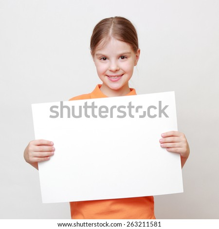 Caucasian little girl with white blank for advertisment - stock photo