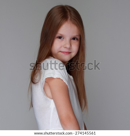 Caucasian lovely little girl with long hair on gray background - stock photo