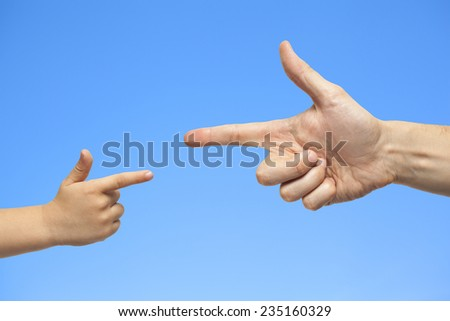 caucasian male and boy hand pointing, or gun gesture, on blue sky background - stock photo