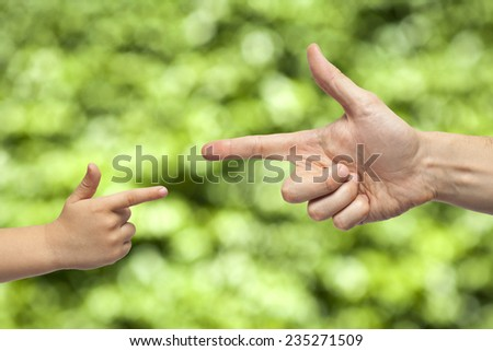 caucasian male and boy hand pointing, or gun gesture, on blurred natural green background - stock photo