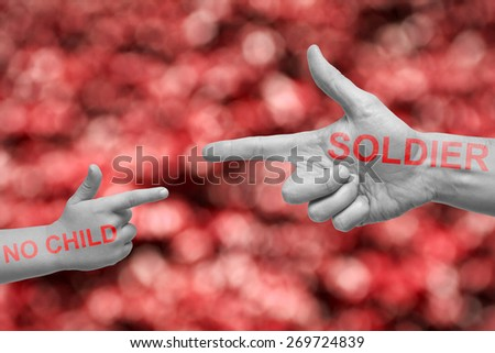 Caucasian male and boy with desaturated hands pointing, or gun gesture, on blurred red background. No Child soldier campaign text in red. - stock photo