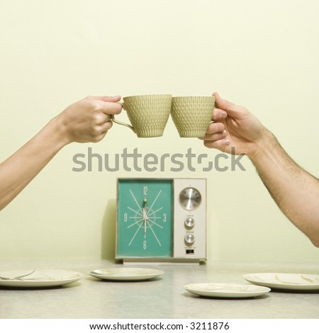 Caucasian male and female hands toasting with coffee cups across retro kitchen table setting. - stock photo