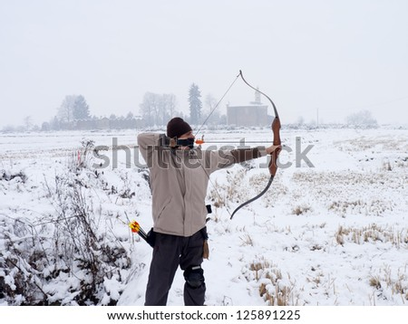 caucasian male archer in a snowy rural place - stock photo