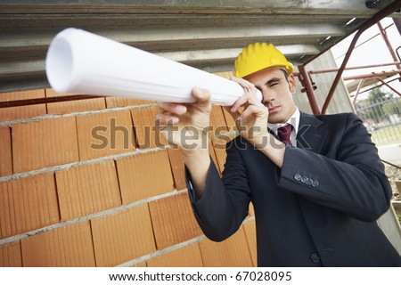 caucasian male architect looking through blueprints scroll. Horizontal shape, waist up, copy space - stock photo
