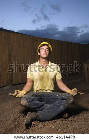 Caucasian male construction worker sits in a yoga meditation pose while wearing a yellow hardhat. Vertical shot. - stock photo