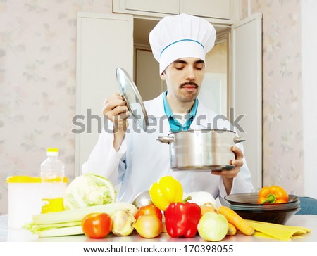 caucasian male cook with pan and vegetables at kitchen - stock photo