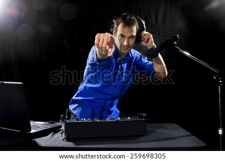 caucasian male dj playing mp3 music with computer and mixer - stock photo