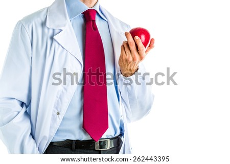 Caucasian male doctor dressed in white coat, blue shirt and red tie is showing a red apple - stock photo