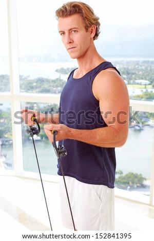 Caucasian male doing resistance training indoors - stock photo