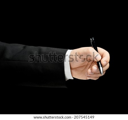 Caucasian male hand in a business suit, holding the pen, low-key lighting composition, isolated over the black background - stock photo