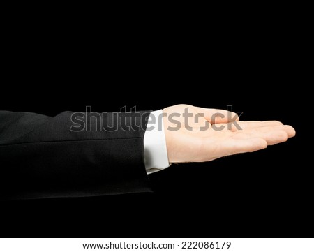 Caucasian male hand in a business suit, opened palm gesture sign, low-key lighting composition, isolated over the black background - stock photo