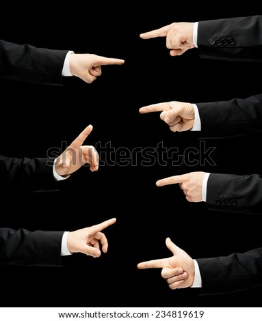 Caucasian male hand in a business suit, pointing with an index finger gesture sign, low-key lighting composition, isolated over the black background - stock photo