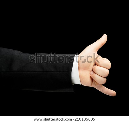 Caucasian male hand in a business suit, showing the be in touch calling gesture sign, low-key lighting composition, isolated over the black background - stock photo