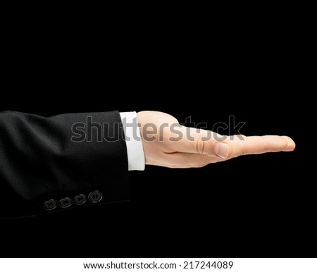 Caucasian male hand in a business suit with a opened palm gesture sign, low-key lighting composition, isolated over the black background - stock photo