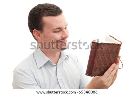 Caucasian male happily reading a leather bound book/journal - stock photo