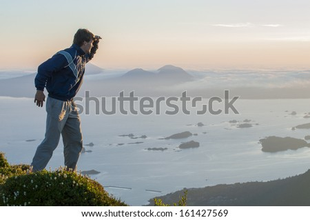 Caucasian male hiker on top of mountain looks out over Sitka Sound during summer sunset on Baranof Island in southeast Alaska