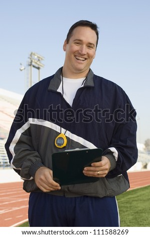Caucasian male instructor holding clipboard - stock photo