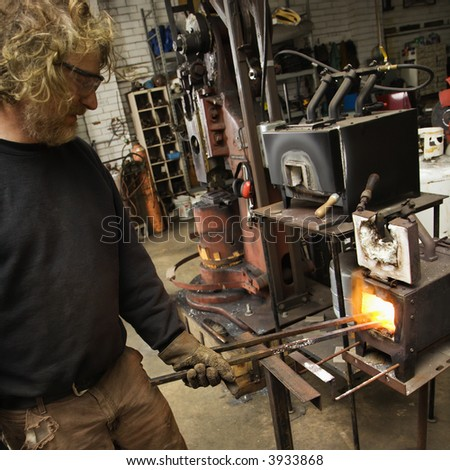 Caucasian male metalsmith heating metal in forge.