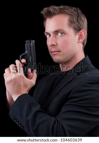 caucasian male model holding a gun isolated on a black background ...