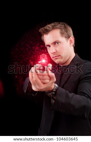 caucasian male model holding a gun isolated on a black background
