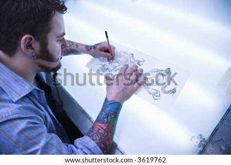 Caucasian male tattoo artist drawing tattoo on light table. - stock photo