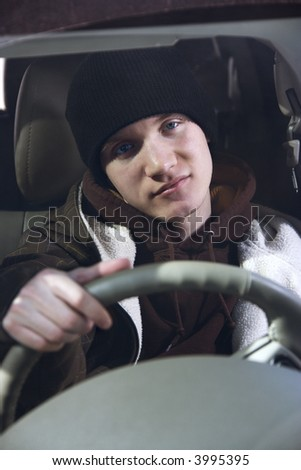 Caucasian male teenager behind the steering wheel. - stock photo