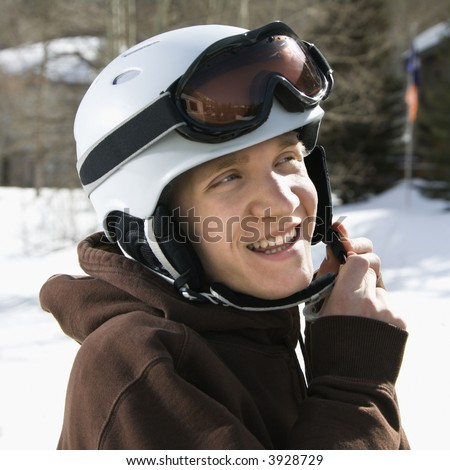 Caucasian male teenager fastening helmet. - stock photo