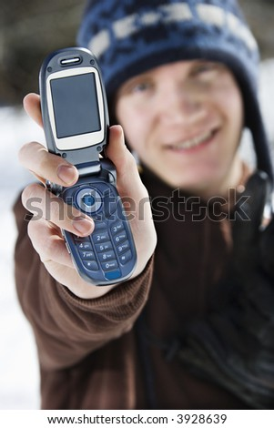 Caucasian male teenager holding out cellphone towards viewer. - stock photo