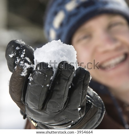 Caucasian male teenager holding snowball out towards viewer. - stock photo