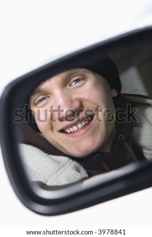 Caucasian male teenager looking at himself in side view mirror of car. - stock photo