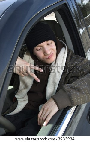 Caucasian male teenager making hand gesture while sitting in car. - stock photo