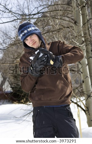 Caucasian male teenager making snowball in winter setting. - stock photo