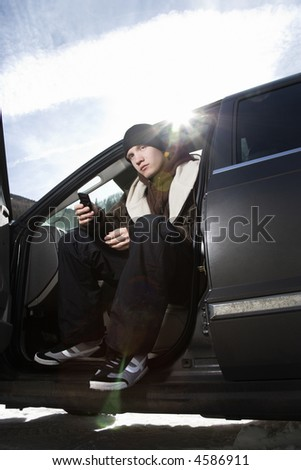 Caucasian male teenager sitting in car holding his cellphone. - stock photo